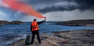 Man holding a red handheld flare