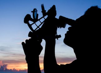 Silhouette of a sailor using a sextant