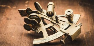 Brass sextant laying on a dark wooden floor