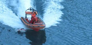 Man overboard drill with rescue boat recovering a dummy from the water