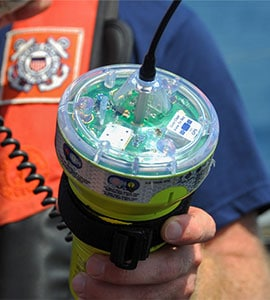 Close up view of a sailor inspecting an EPIRB