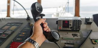 VHF handset in a sailor's hand with the base station in the background