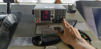 "Hand reaching out to press the ""CH16"" button on a VHF radio"