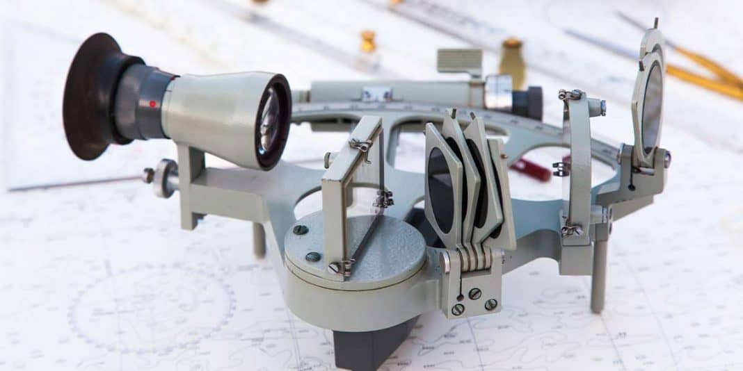 Metal sextant sitting on a navigational chart