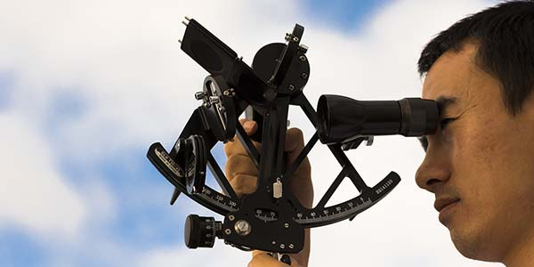 Close up of officer using a sextant
